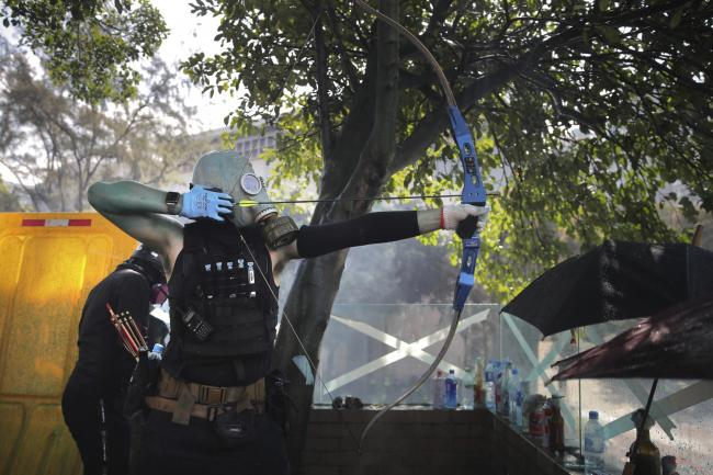 A protestor prepares to fire a bow and arrow in Hong Kong