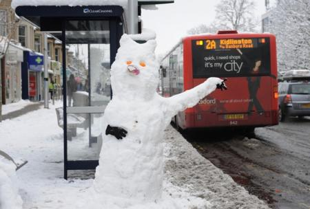 Snow chance: snowman waits in vain for a bus in icy Oxford