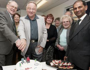 DR Harry Hill (left) cuts the cake with patient Chris Phillipson to celebrate the 40th anniversary with clinical lead Dr Richard D'Souza (far right).