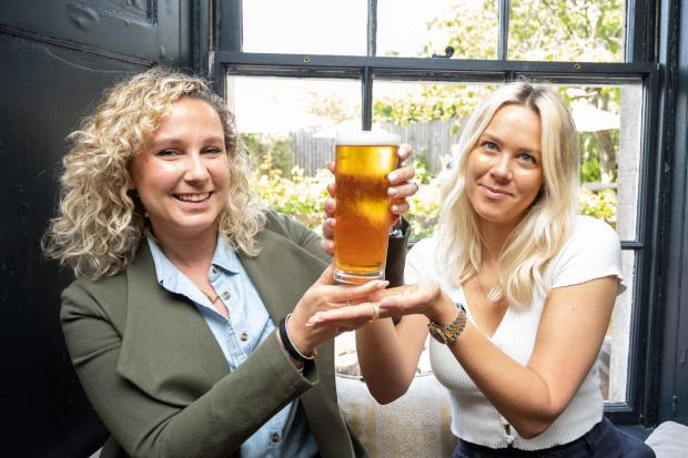 PRICEY PINT: Winning bidders Olivia, right, and Isabelle Cundy who, along with other family members, bid £755 for the first pint pulled at The Packhorse pub in South Stoke