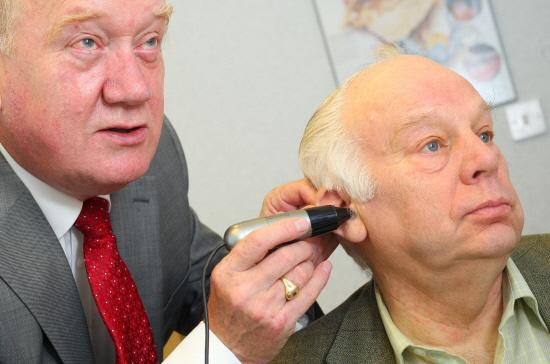 Somerset County Gazette: £5 FOR LEGION: Ted Garrett, hearing aid audiologist, gives Bill Bestford a hearing test