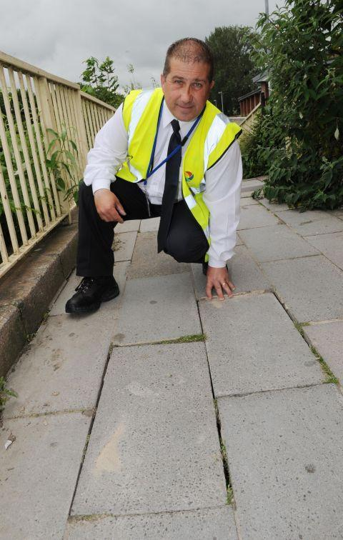 Mark Bundy next to some of the uneven paving slabs. PHOTO: Geoff Hall
