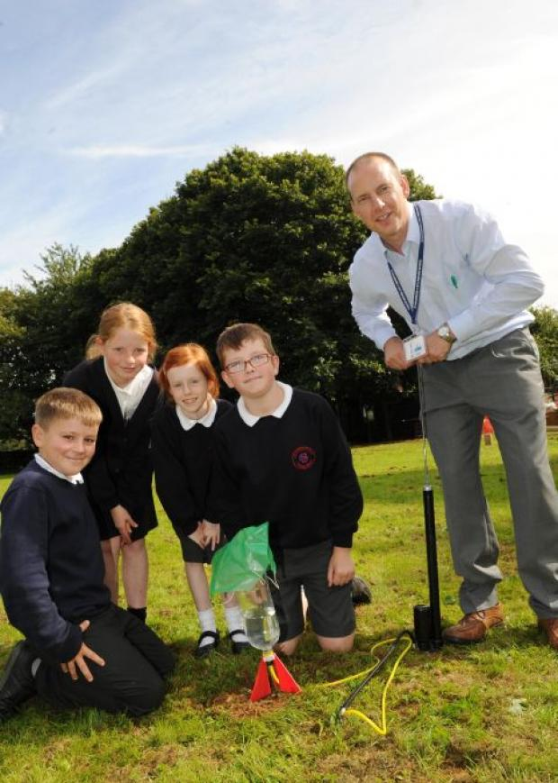 Teacher Jason Pook and pupils launch a rocket at their NASA day