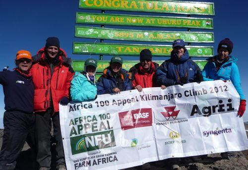 James Hawthorne is pictured in the middle wearing a red jacket and black hat with his fellow trekkers at the top of Mount Kilimanjaro.