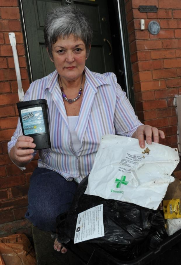 Veronica Roach with a bag of needles dumped outside her home on Priory Avenue.