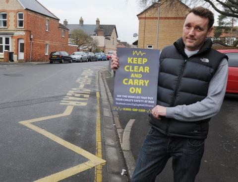 Mark Williams holds up a poster outside North Town Primary School which he hands to parents parking on the zigzag zone.