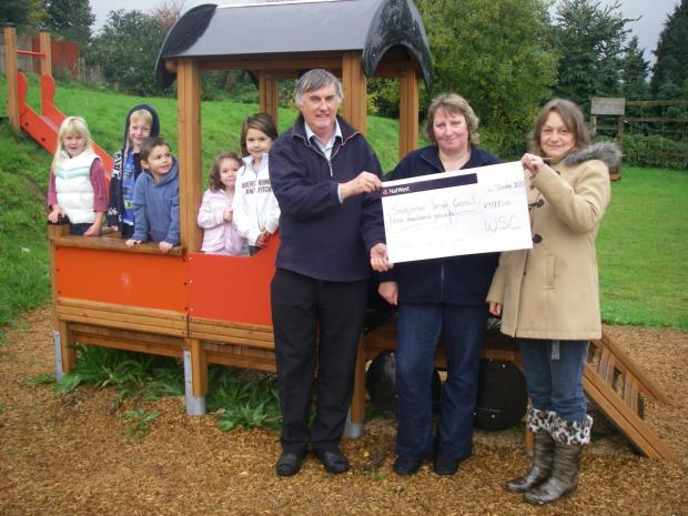 PLAY TIME: Cllr David Westcott of West Somerset Council, presents the cheque to Michelle Moss, Stogumber play area committee treasurer, and Lorraine Tribe, Stogumber play area committee chairman, as children enjoy the new equipment. PHOTO: Submitted.