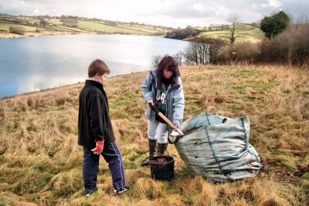 TWO members of the Dulverton & District Young People's Project get stuck in planting apple trees. PHOTO: Submitted.