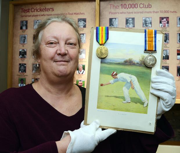 Louise Perrin with Len Braund's First World War medals and a picture of the cricketer in action.