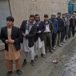 Afghan men line up for the registration process before they cast their votes at a polling station in Kabul (AP)