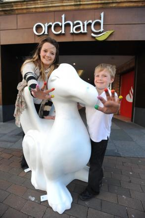 Sophie Durdan-Adams and Sam Durdan-Bone are pictured getting ready to put their print on a blank dragon outside Taunton's orchard shopping centre.