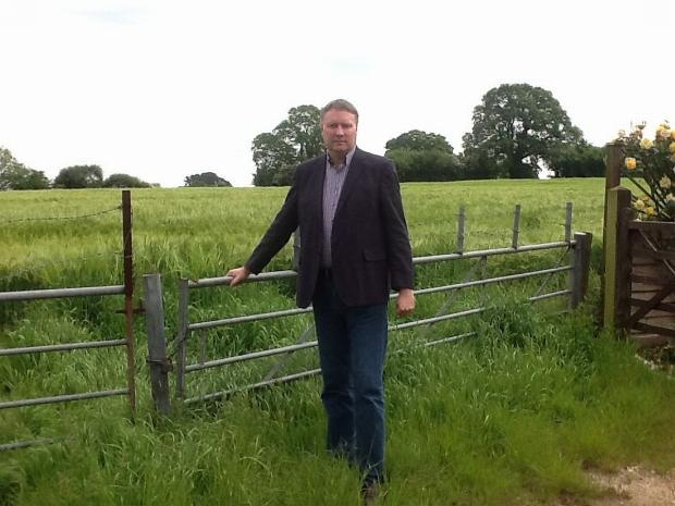 Cllr Ross Henley is pictured in Beech Hill next to the proposed access site to the estate east of Wellington.