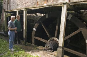 Pictured, from left, are Mike Bushen and Robert Downes, of Exmoor National Park Authority, inspecting restored water wheel.
