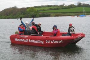 TAKING TO THE WATER: Jo Smith helms the new boat with volunteers and visitors