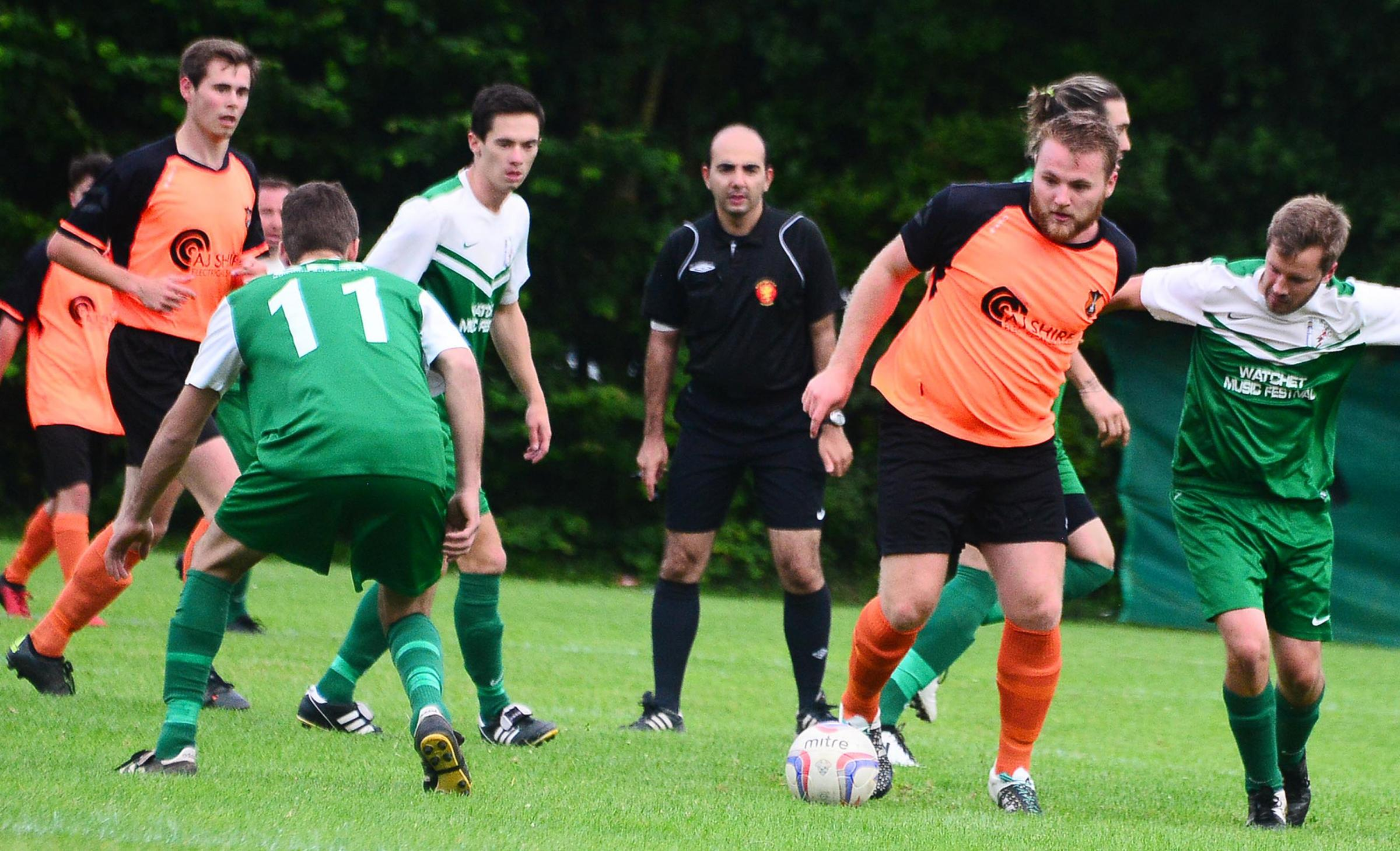 WELLINGTON'S Tom Ellis (orange kit) in action against Watchet Town on Tuesday night. The friendly match at Richard Huish College ended 1-1.