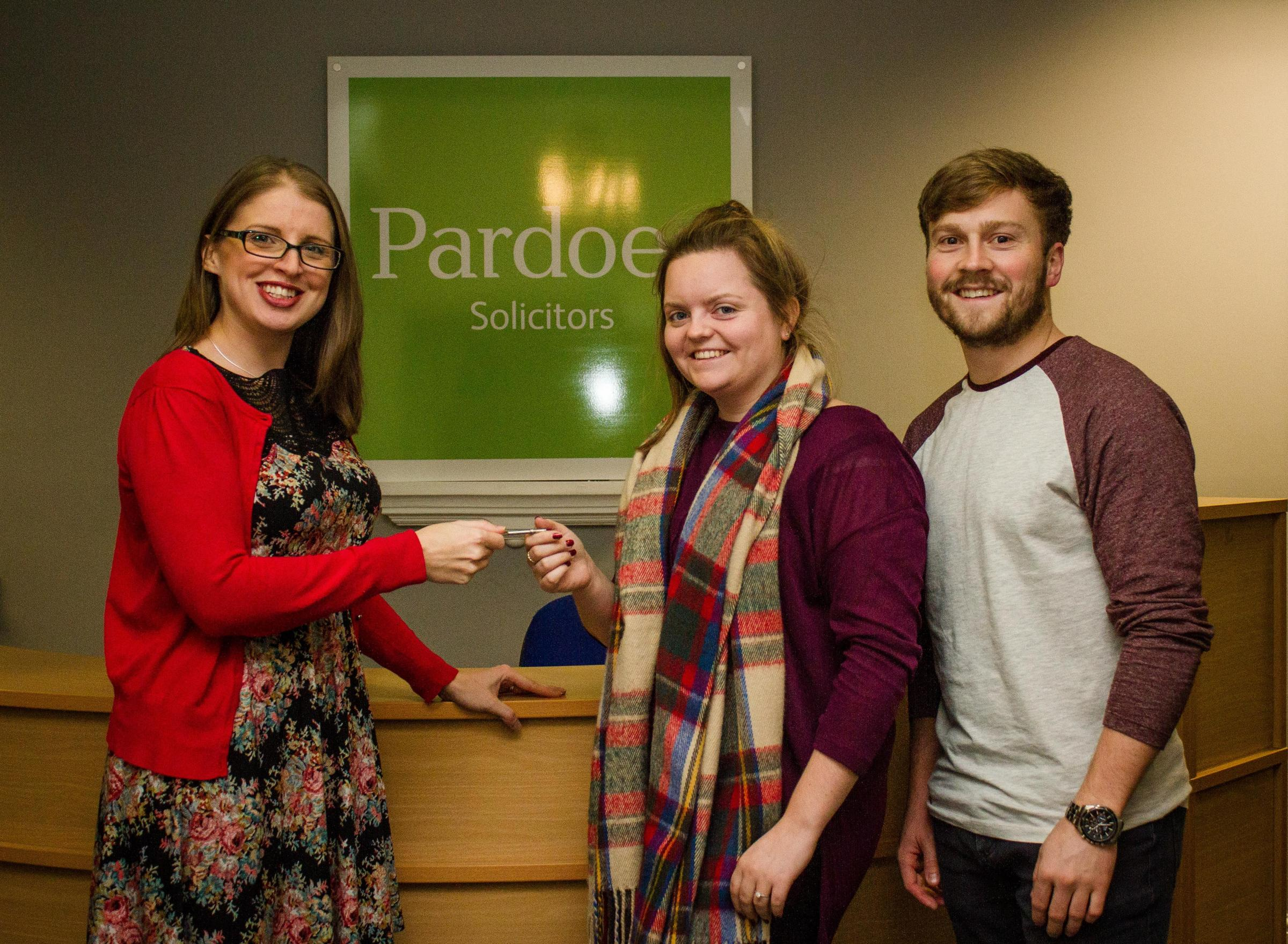 Laura Godfrey, from Pardoes Solicitors, handing Siân Woodhouse and Jacob Smith the keys to their new Taunton home