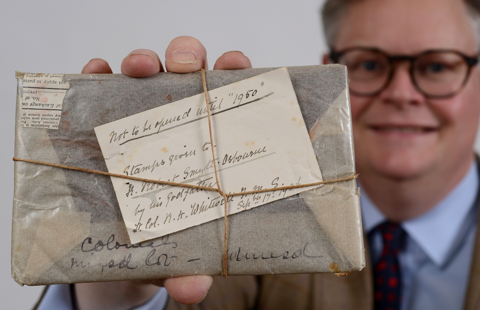 SEALED: Richard Bromell with an unopened packet of stamps, put away in a bank vault in 1926 and now opened in 2018