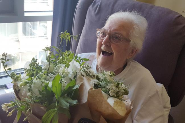 Pauline Clayton, 89, a patient at St Joseph's Hospice in Hackney with flowers from the royal wedding (Helen William/PA)