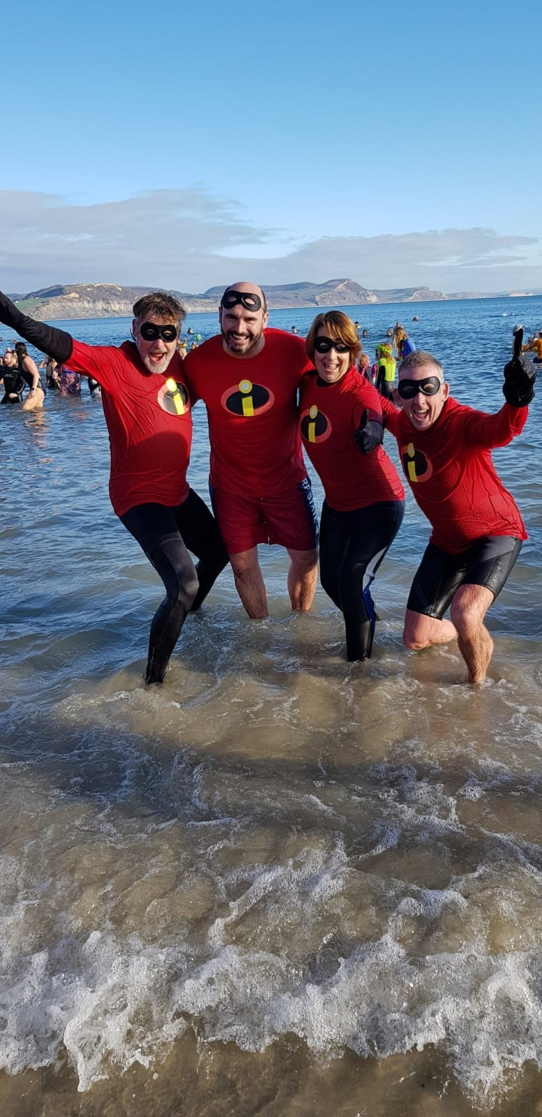 SUPERHEROES: Viv Duncan pictured with three of her fundraising friends, Dave Mann, Dave Oaten and Patrick Coll, at the Lyme Regis beach on New Year's Day