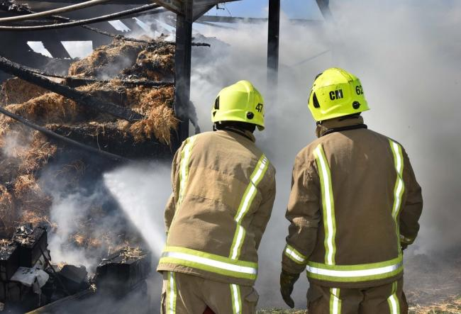 FIRE: A general view of firefighters damping down a barn fire